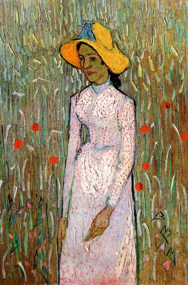 Muchacha de pie delante de un campo de trigo